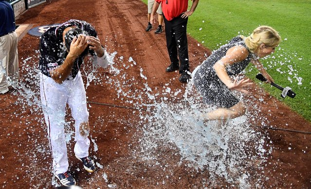 Washington Nationals third baseman Anthony Rendon and reporter Alex Chappell are doused with water after the game against the Miami Marlins in Washington on August 30, 2019. (Photo by Brad Mills/USA TODAY Sports)