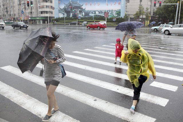 Pedestrians hold their umbrellas against strong wind as Typhoon Chan-Hom hits Shanghai, China, July 11, 2015. More than 865,000 people have been evacuated from China's eastern province of Zhejiang ahead of Saturday's expected landfall of Typhoon Chan-Hom, state news agency Xinhua said. (Photo by Reuters/Stringer)