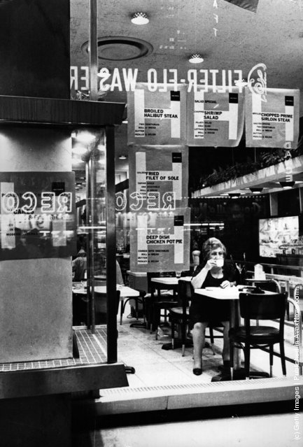 1968:  A woman sitting in a Times Square cafeteria, New York