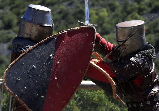 Men dressed like medieval knights  attend a battle in front a castle during the traditional medieval festivities in Saint jean de bueges, Southern France, 04 May 2014.  (Photo by Guillaume Horcajuelo/EPA)