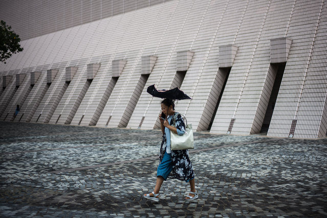 A woman uses an umbrella as she walks along a promenade that runs along Victoria Harbour in Hong Kong on September 13, 2018. (Photo by Anthony Wallace/AFP Photo)