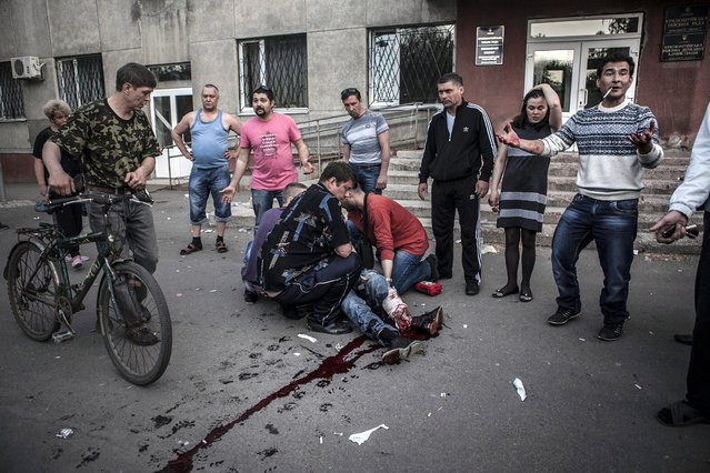 Local residents watch as others give first aid to a man who was shot in the leg by Ukranian militia in the village of Krasnoarmisk, Ukraine, 11 May 2014. Eyewitness said that Ukranian militia tried to stop the referendum voters briefly taking the City Hall of Krasnoarmisk, where unarmed pro-Russian supporters were gathering. (Photo by EPA/Maysun)
