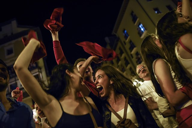 "People hold up red kerchiefs as they sing a song ""Pobre de Mi"", at the end of  San Fermin Festival on the midnight, in Pamplona, northern Spain, Wednesday, July 15, 2015. (Photo by Alvaro Barrientos/AP Photo)"
