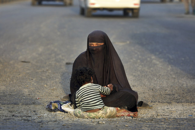In this Monday, September 23, 2019, a woman waits for alms as she sits with her child in a street on the outskirts of Kabul, Afghanistan. (Photo by Ebrahim Noroozi/AP Photo)