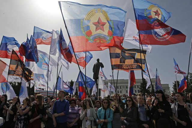 People hold flags as they take part in a May Day rally in rebel-held Luhansk, Ukraine on May 1, 2017. (Photo by Alexander Ermochenko/Reuters)
