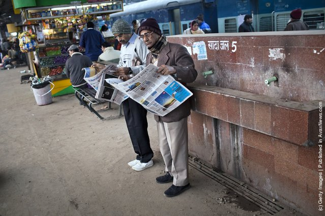 Men read newspapers as they wait for their train at the Nizamuddin Railway Station in New Delhi, India
