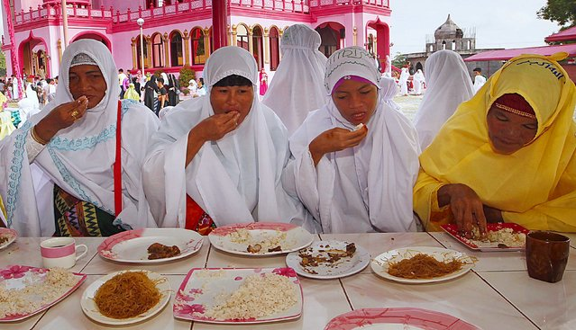 Filipino Muslims eat a meal after attending the morning prayers of Eid al-Fitr holiday, marking the end of the holy month of Ramadan, outside the Pink Mosque in Datu Saudi Ampatuan town, Maguindanao province in southern Philippines July 17, 2015. (Photo by Marconi Navales/Reuters)