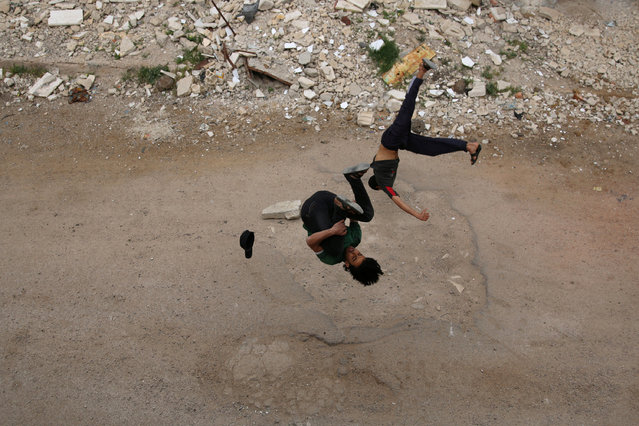 Parkour coach Ibrahim al-Kadiri (L), 19, and Muhannad al-Kadiri, 18, demonstrate their Parkour skills in the rebel-held city of Inkhil, west of Deraa, Syria, April 7, 2017. (Photo by Alaa Al-Faqir/Reuters)