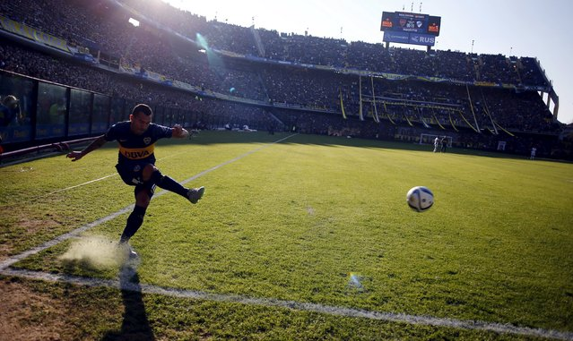 Boca Juniors' Carlos Tevez takes a free kick during their Argentine First Division soccer match against Quilmes in Buenos Aires July 18, 2015. Tevez was officially unveiled on July 13 in a 6.5 million euros ($7.15 million) transfer from Juventus. Thousands of fans of the popular club from the port district of La Boca packed La Bombonera stadium to welcome Tevez home from a decade abroad the day after the team went top of the Argentine league championship. (Photo by Marcos Brindicci/Reuters)