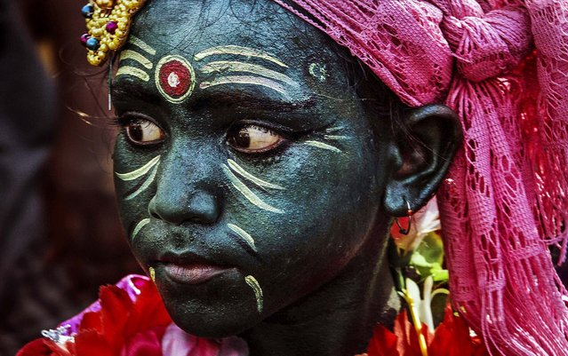 A boy with his face painted participates in a procession for the Chandan Yatra festival in Puri, India, on May 21, 2014. Chandan Yatra means Sandalwood Voyage, where devotees smear the deities of the Lord with cooling sandalwood paste. (Photo by Biswaranjan Rout/Associated Press)