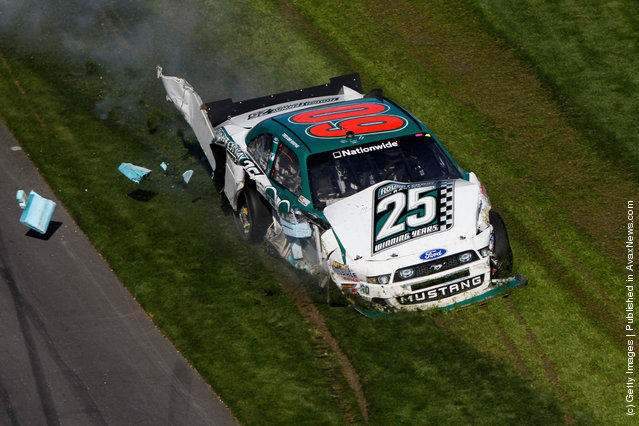 Trevor Bayne drives the wrecked #60 Roush Fenway Racing Ford through the grass after being involved in a last lap on track incident during the NASCAR Nationwide Series DRIVE4COPD 300 at Daytona International Speedway