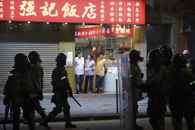 Onlookers stand in the entrance of a restaurant as police in riot gear gather during a protest in Hong Kong, Saturday, November 2, 2019. Pro-democracy protesters attacked the office of Chinese news agency Xinhua for the first time Saturday, after familiar chaos downtown that saw police and demonstrators trading petrol bombs, tear gas and water cannon in the 22nd straight weekend of unrest. (Photo by Kin Cheung/AP Photo)