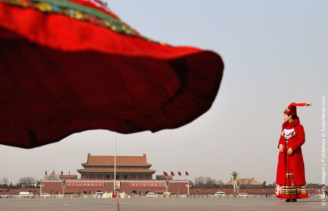 Hostesses dressed in Chinese ethnic minority dresses stand at the Tiananmen Square before the third plenary meeting of the National People's Congress (NPC) on March 9, 2012 in Beijing, China
