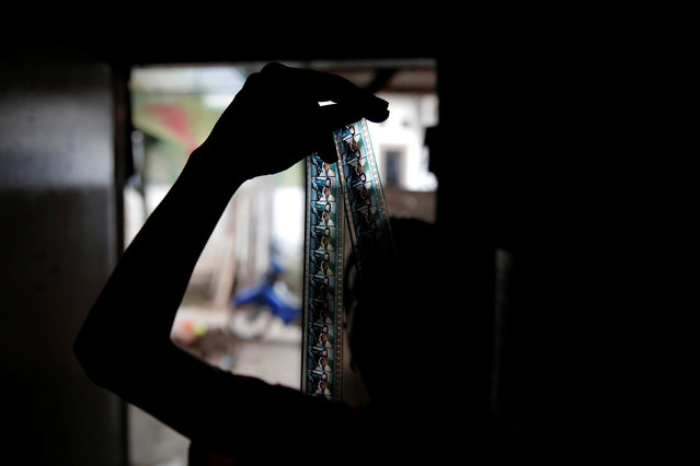 Kamaluddin checks a 35mm film strip at his workshop in Tangerang, Indonesia, March 11, 2017. (Photo by Reuters/Beawiharta)
