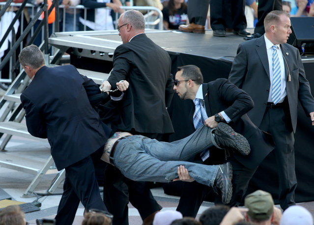 Secret Service agents remove a man from the crowd during a campaign rally for Democratic presidential candidate, Sen. Bernie Sanders, I-Vt., at Frank Ogawa Plaza in Oakland, Calif., on Monday, May 30, 2016. A group of animal rights activists briefly interrupted the Sanders rally in Northern California when they jumped barricades and tried to rush the podium. Sanders' security stopped the protesters before they could reach Sanders, who was addressing supporters at the rally and continued his speech within minutes of the disruption. (Photo by Anda Chu/Oakland Tribune via AP Photo)