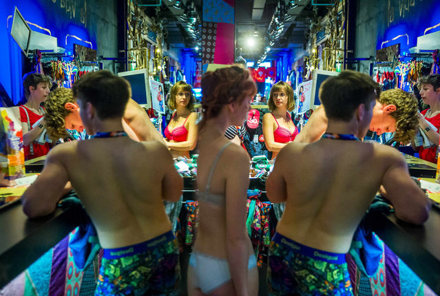 People dressed in underwear run into a store to pick free clothes during a promotional event starting the summer sale at an outlet of the Desigual clothing retailer in Berlin, June 20, 2014. Desigual treated the first 100 customers with a free outfit if they stripped down to their underwear for the first day of the outlet's summer sale. (Photo by Thomas Peter/Reuters)