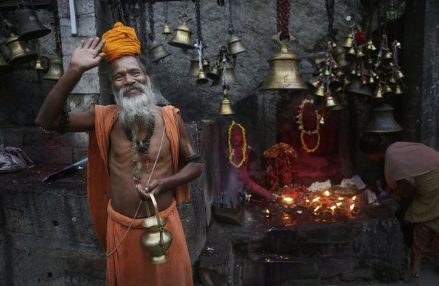 An Indian Sadhu, or Hindu holy man, waves to the camera at the Kamakhya temple in Gauhati, India, Saturday, June 21, 2014. The annual Ambubasi festival begins Sunday where hundreds of tantric Sadhus, holy men from an esoteric form of Hinduism, gather to perform rituals at the temple. (Photo by Anupam Nath/AP Photo)