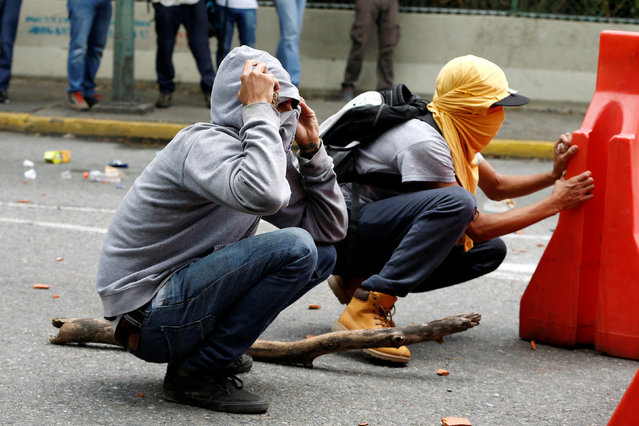 Demonstrators take cover as they clash with riot police officers during a protest called by university students against Venezuela's government in Caracas, Venezuela, June 9, 2016. (Photo by Carlos Garcia Rawlins/Reuters)