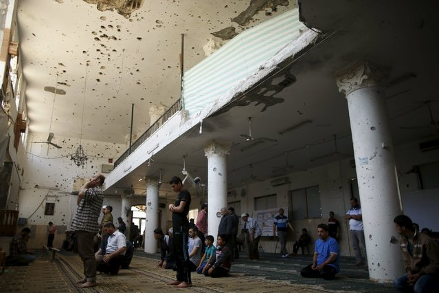 Palestinians pray inside a mosque that witnesses said was badly damaged by Israeli shelling during a 50-day war last summer, in the east of Gaza City May 6, 2015. (Photo by Mohammed Salem/Reuters)