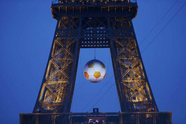 A giant soccer ball hangs from the Eiffel Tower during the France v Romania EURO 2016 Group A soccer match, in Paris, France, June 10, 2016. (Photo by Gonzalo Fuentes/Reuters)