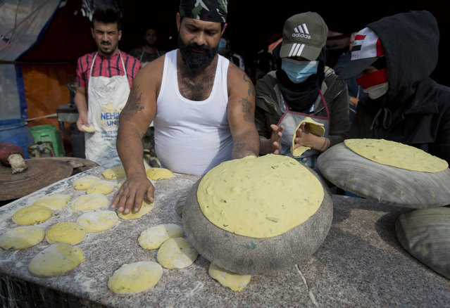In this photo taken Monday, December 9, 2019, a volunteer chef serves free portions of the popular Arouk bread, wheat flour mixed with meat and onions, to protester in the center of Baghdad, Iraq. (Photo by Nasser Nasser/AP Photo)