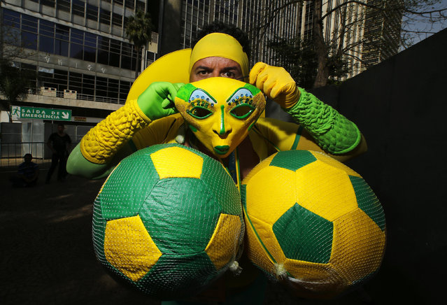 A Brazil fan puts on his costume before watching a telecast of the 2014 World Cup soccer match between Brazil and Chile, at a FIFA fan area in Sao Paulo June 28, 2014. (Photo by Ivan Alvarado/Reuters)