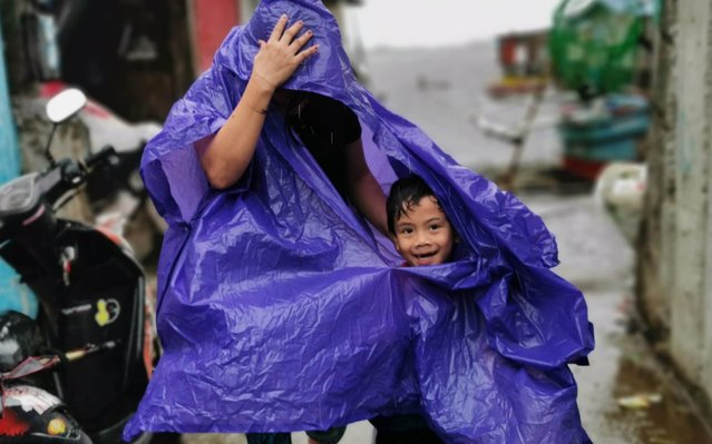Villagers covers their heads during strong winds brought by Typhoon Kammuri, in Cavite City, Philippines, 03 December 2019. Typhoon Kammuri made landfall on 02 December and forced the closure of Ninoy Aquino International Airport in Manila. (Photo by Francis R. Malasig/EPA/EFE/Rex Features/Shutterstock)