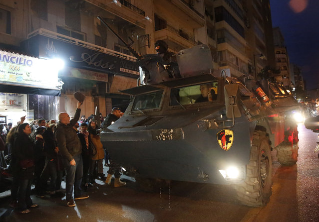 A police armored personnel carrier passes next of anti-government protesters outside police headquarters, as they demand the release of those taken into custody the night before, in Beirut, Lebanon, Wednesday, January 15, 2020. Lebanese security forces arrested 59 people, the police said Wednesday, following clashes overnight outside the central bank as angry protesters vented their fury against the country's ruling elite and the worsening financial crisis. (Photo by Hussein Malla/AP Photo)