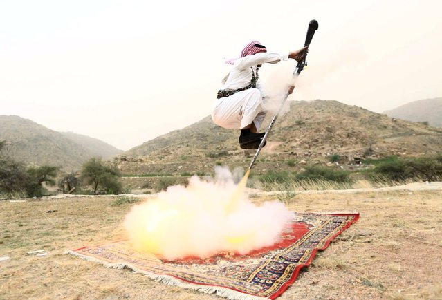 A man fires a weapon as he dances during a traditional excursion near the western Saudi city of Taif, August 8, 2015. Saudis usually party in such excursions as they celebrate weddings or graduations. (Photo by Mohamed Al Hwaity/Reuters)