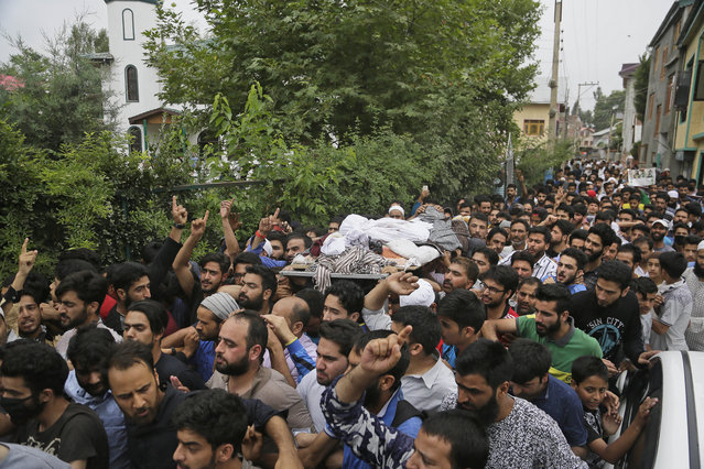 Kashmiri people carry the body of a local rebel Aqib Ahmad during his funeral procession in Srinagar, Indian controlled Kashmir, Wednesday, July 12, 2017. Anti-India protests and clashes erupted in the main city in Indian-controlled Kashmir after three men police identified as Kashmiri rebels were killed in a gunbattle with government forces. (Photo by Mukhtar Khan/AP Photo)