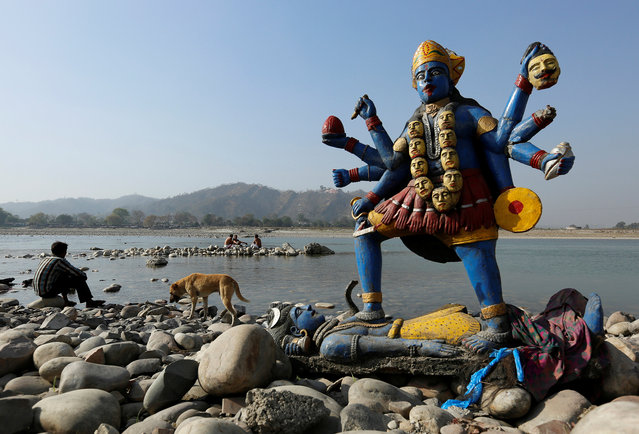 A man sits next to a damaged idol of Hindu goddess Kali which was taken out after its immersion in the river Ganges in Haridwar, India, March 29, 2017. (Photo by Danish Siddiqui/Reuters)