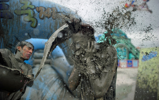 A reveller throws a bucket of mud during the 17th Boryeong mud festival at Daecheon beach in Boryeong, 150 kilometers southwest of Seoul, on July 18, 2014. The annual festival aims to promote the use of the mineral-rich mud for cosmetic skin-care and to promote tourism in the region. (Photo by Ed Jones/AFP Photo)