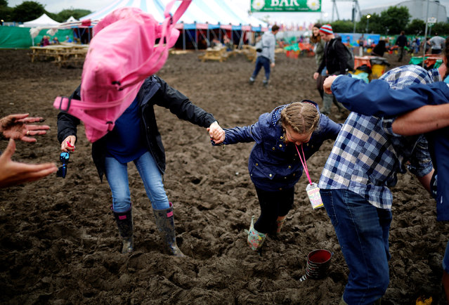 Revellers try to walk out of the mud at Worthy Farm in Somerset during the Glastonbury Festival, Britain, June 26, 2016. (Photo by Stoyan Nenov/Reuters)