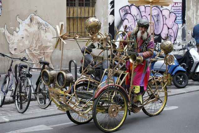 "French artist Gino rides the ""Celestial Cyclo"" tricycle built by him in Le Marais neighbourhood in Paris, France, August 15, 2015. (Photo by Pascal Rossignol/Reuters)"