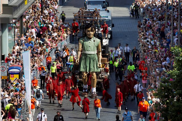 A girl giant marionette is steered through the centre of Liverpool as she and two other giants, a grandmother and a dog, parade through the streets, in Liverpool, England, Friday, July 25, 2014. The huge figures begin the three-day commemoration of World War One. Royal de Luxe, the French street theatre company organised the event. (Photo by Jon Super/AP Photo)