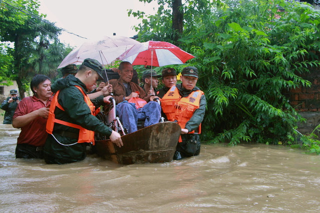 Rescuers save a resident from a flooded area in Anqing, Anhui Province, China, July 2, 2016. (Photo by Reuters/Stringer)