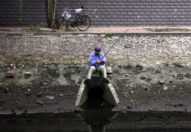A man sits atop a drain as he fishes at a polluted canal in central Beijing October 26, 2010. Locals fish in the canals that run through the city before the canals freeze during winter months, making fishing much harder. (Photo by David Gray/Reuters)