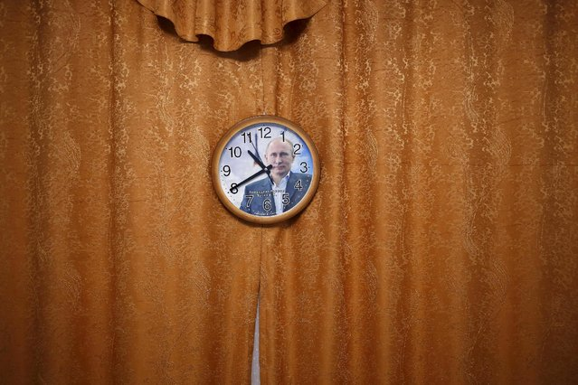 A wall clock with a picture of Russian President Vladimir Putin is seen in this photo illustration taken in a hotel room in Kazan, Russia, July 31, 2015. (Photo by Stefan Wermuth/Reuters)