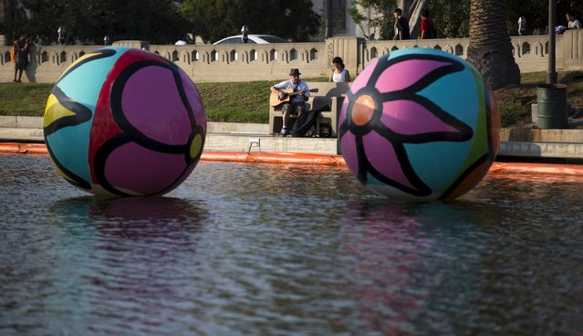 "A street performer is pictured between inflated spheres in MacArthur Park Lake during the installation of Portraits of Hope's exhibition ""Spheres at MacArthur Park"" in Los Angeles, California August 21, 2015. (Photo by Mario Anzuoni/Reuters)"