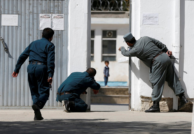 Afghan policemen try to rescue a child at the site of a suicide attack followed by a clash between Afghan forces and insurgents after an attack on a Shi'ite Muslim mosque in Kabul, Afghanistan on Friday, August 25, 2017. (Photo by Omar Sobhani/Reuters)