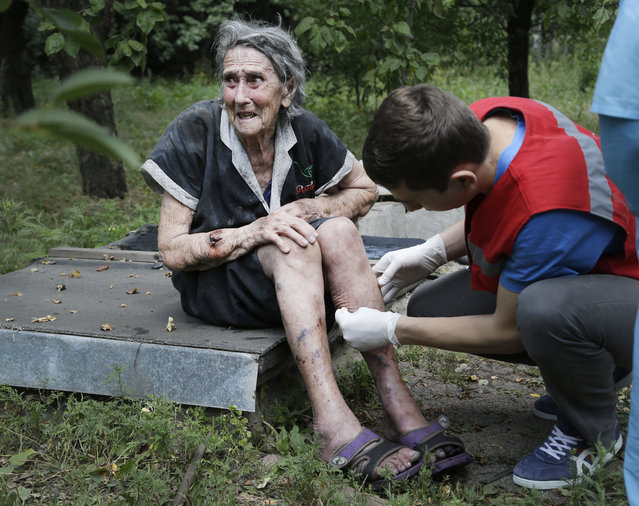 "A wounded Ukrainian woman receiving treatment after shelling in Donetsk, eastern Ukraine, Sunday, August 10, 2014. Fighting raged Sunday in the eastern Ukrainian city of Donetsk despite a request from the pro-Russian rebels there for a cease-fire to prevent a ""humanitarian catastrophe"". One person was killed and 10 injured in shelling that started early Sunday morning and continued into the day, city council spokesman Maxim Rovinsky told The Associated Press. (Photo by Sergei Grits/AP Photo)"
