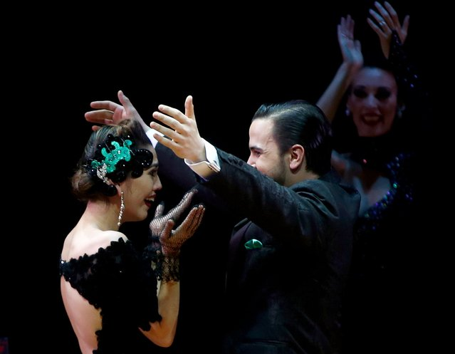 Ezequiel Lopez (C) and Camila Alegre from Argentina, who are representing the city of San Fernando, embrace after they won the Tango World Championship in Stage style in Buenos Aires August 27, 2015. (Photo by Marcos Brindicci/Reuters)