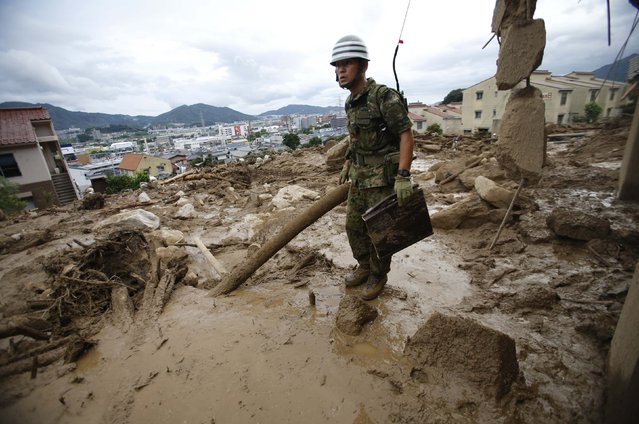 A Japan Self-Defense Force soldier searches for survivors at a site where a landslide swept through a residential area at Asaminami ward in Hiroshima, western Japan, August 20, 2014. At least 36 people, including several children, were killed in Japan on Wednesday, when landslides triggered by torrential rain slammed into the outskirts of the western city of Hiroshima, and the toll could rise further, police said. (Photo by Toru Hanai/Reuters)