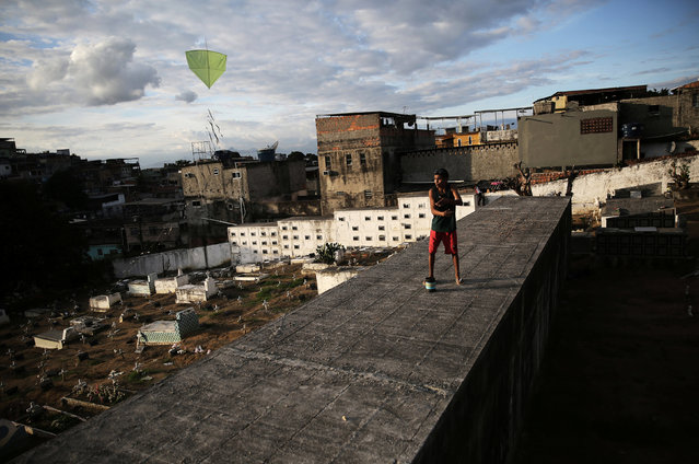 A boy flies his kite in a cemetery in the Vila Operaria Favela of Rio de Janeiro, Brazil, June 26, 2016. (Photo by Nacho Doce/Reuters)