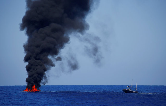 The Libyan Coast Guard burns a rubber boat at the end of a search and rescue (SAR) operation headed by the SOS Mediterranee organisation, with the MV Aquarius rescue ship (not pictured) in the Mediterranean Sea, off the Libyan Coast, September 14, 2017. (Photo by Tony Gentile/Reuters)