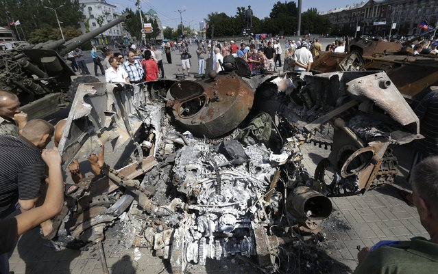 People inspect damaged heavy hardware from the Ukrainian army during an exhibition in a central square in Donetsk, eastern Ukraine, Sunday, August 24, 2014. Ukraine has retaken control of much of its eastern territory bordering Russia in the last few weeks, but fierce fighting for the rebel-held cities of Donetsk and Luhansk persists. (Photo by Sergei Grits/AP Photo)