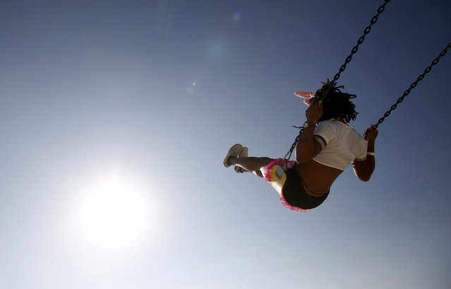 """Adorable, her Playa name, rides a swing during the Burning Man 2015 """"Carnival of Mirrors"""" arts and music festival in the Black Rock Desert of Nevada, August 31, 2015. (Photo by Jim Urquhart/Reuters)"""
