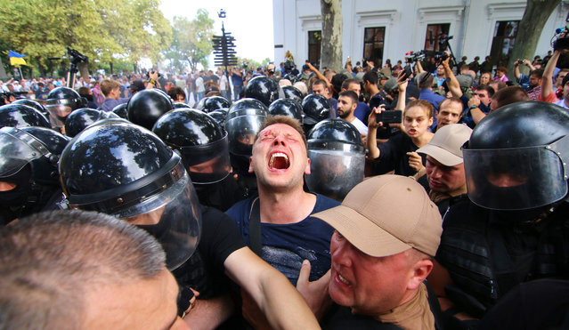 Activists clash with police as they storm the Odessa city hall on September 20, 2017. Some 20 police and 16 soldiers of the National guard were wounded during the clashes, as some 500 protesters demanded the mayor' s resignation and the dissolving of the city council following the deaths of three girls in a fire at a the Victoria children' s camp on September 16, 2017, close to Odessa. (Photo by Aleksandr Gimanov/AFP Photo)