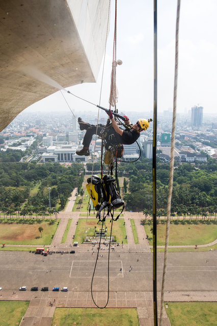 Two men clean the National Monument in Indonesia. (Photo by Caters News Agency)