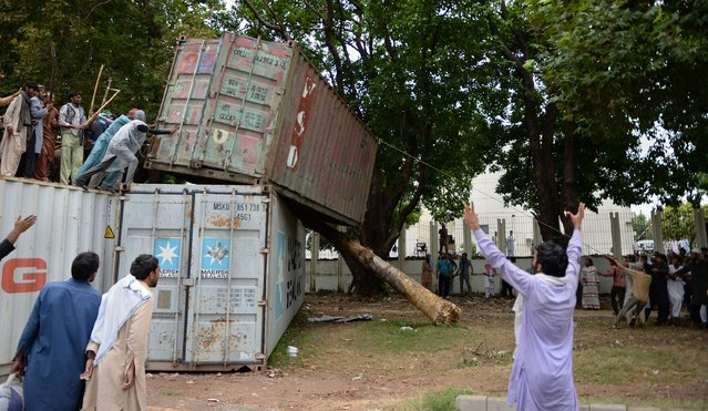 Supporters of cricketer-turned-politician Imran Khan and cleric Tahirul Qadri work to topple a cargo container during a protest near the parliament building in Islamabad, on September 2, 2014. Khan and Qadri supporters have been protesting in the capital since August 15 to try to oust Prime Minister Nawaz Sharif, triggering a crisis that has raised the specter of military intervention in a country ruled for half its history by the army. (Photo by Asif Hassan/AFP Photo)